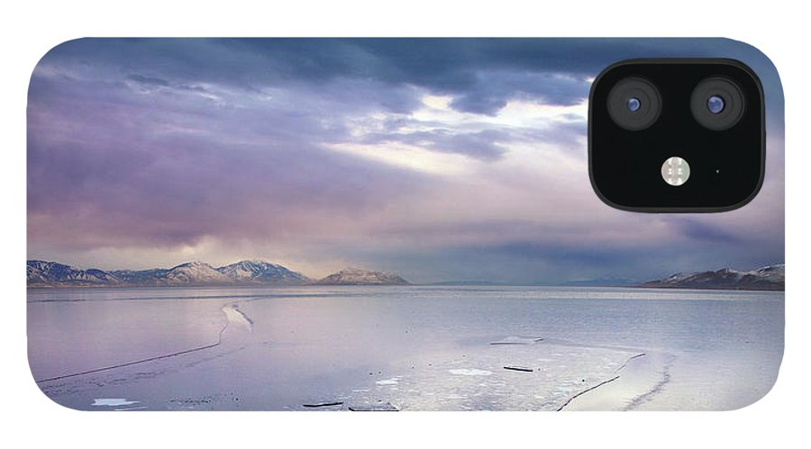 Scenics IPhone 12 Case featuring the photograph Storm Clouds Clearing Over Icy Lake by Utah-based Photographer Ryan Houston