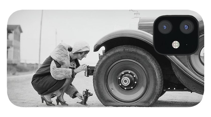 People IPhone 12 Case featuring the photograph Woman Changing Flat Tire On Car by H. Armstrong Roberts