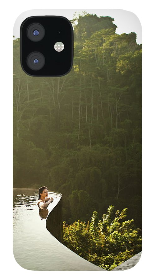Tropical Rainforest IPhone 12 Case featuring the photograph Woman In Infinity Pool At Sunrise. Bali by Matthew Wakem