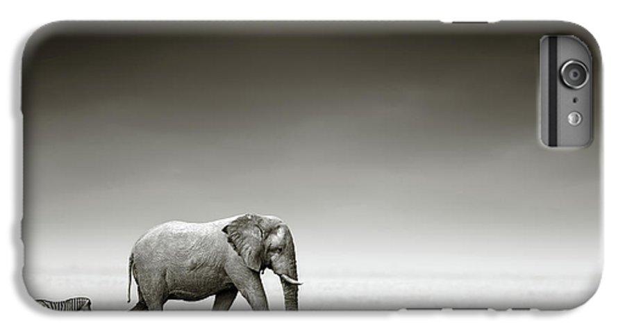 Elephant; Zebra; Behind; Follow; Huge; Big; Grass; Grassland; Field; Open; Plains; Grassfield; Dark; Sky; Together; Togetherness; Art; Artistic; Black; White; B&w; Monochrome; Image; African; Animal; Wildlife; Wild; Mammal; Animal; Two; Moody; Outdoor; Nature; Africa; Nobody; Photograph; Etosha; National; Park; Loxodonta; Africana; Walk; Namibia IPhone 6 Plus Case featuring the photograph Elephant With Zebra by Johan Swanepoel
