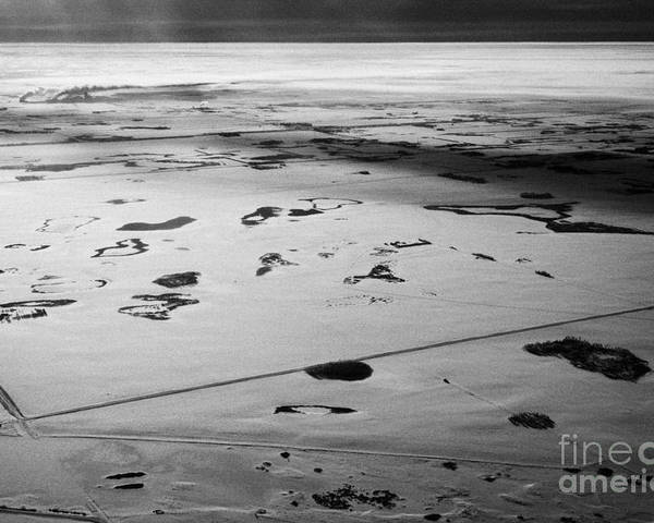 Aerial Poster featuring the photograph aerial view of snow covered prairies and remote isolated farmland in Saskatchewan Canada by Joe Fox