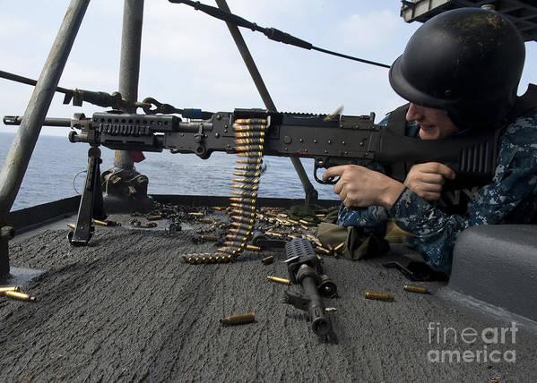 Military Poster featuring the photograph A Sailor Fires An M-240b Machine Gun by Stocktrek Images