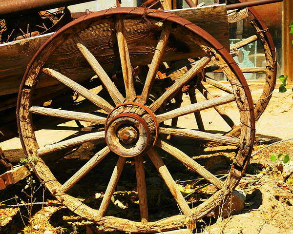 Rounds Poster featuring the photograph A Wagon Wheel by Jeff Swan
