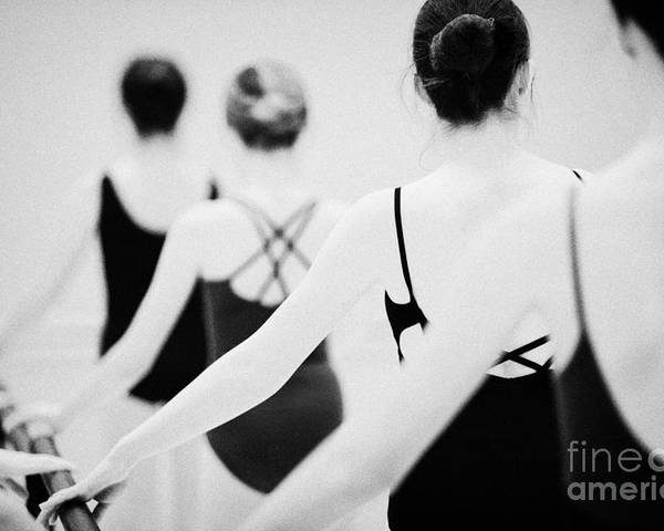 Ballet Poster featuring the photograph Female Teenage Ballet Students Holding On To A Ballet Barre At A Ballet School In The Uk by Joe Fox