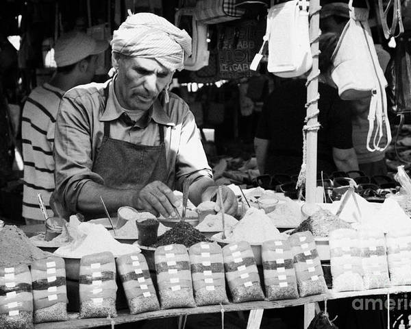 Tunisia Poster featuring the photograph Local Arab Man Measuring Out A Quantity Of Spice For Sale On Stall Of Spices At The Market In Nabeul Tunisia by Joe Fox