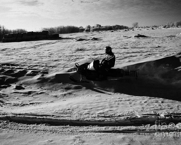 Man Poster featuring the photograph man on snowmobile crossing frozen fields in rural Forget Saskatchewan Canada by Joe Fox