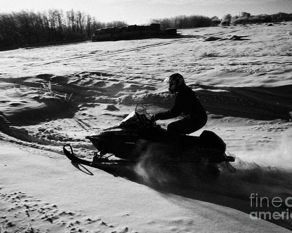 Man Poster featuring the photograph man on snowmobile crossing frozen fields in rural Forget Saskatchewan by Joe Fox