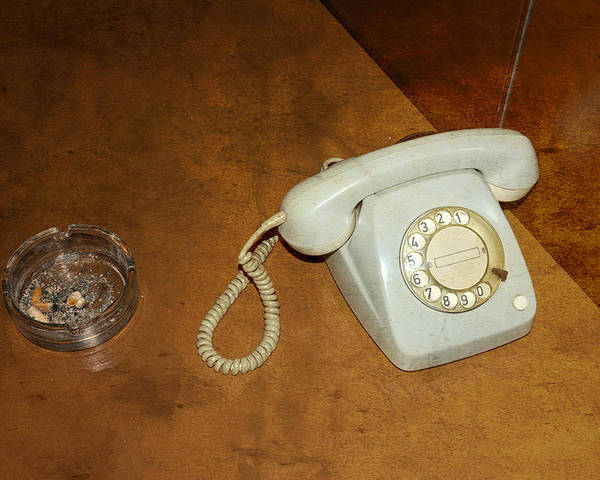 Phone Poster featuring the photograph Old Telephone And Ashtray On Brown Table by Matthias Hauser