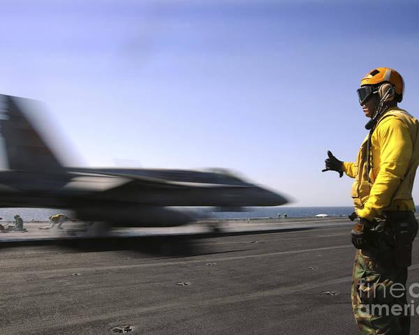 Uss Enterprise Poster featuring the photograph A Sailor Ensures An Fa-18c Hornet by Stocktrek Images