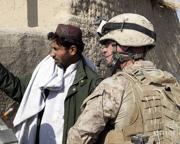 Marines Poster featuring the photograph A Soldier Talks To A Local Villager by Stocktrek Images