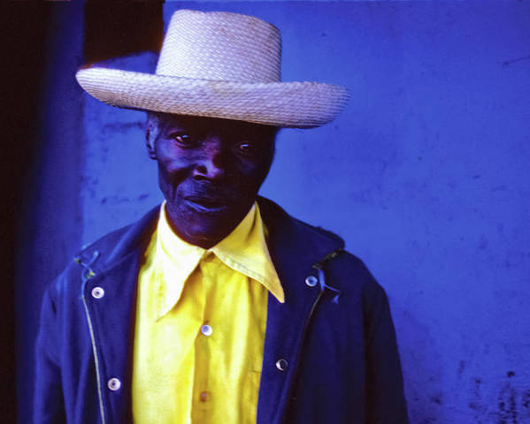 Haiti Poster featuring the photograph Blue Man With Yellow Hat And Shirt by Johnny Sandaire