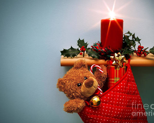 Christmas Poster featuring the photograph Christmas Stocking Filled With Presents With Candle And Holly. by Richard Thomas