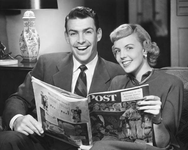 30-34 Years Poster featuring the photograph Couple Sitting On Sofa, Holding Magazine, (b&w), Portrait by George Marks