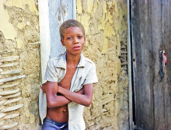 Boy Poster featuring the photograph Haitien Boy Leaning On Wall by Johnny Sandaire