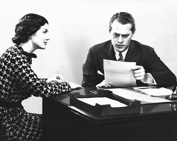 25-29 Years Poster featuring the photograph Secretary Assisting Businessman Reading Document At Desk, (b&w) by George Marks