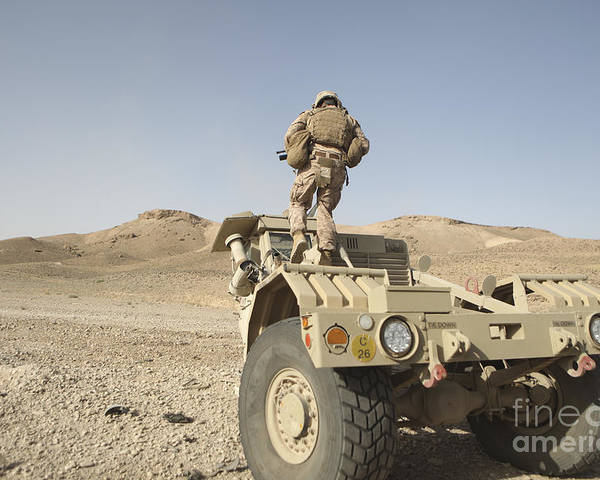 Operation Enduring Freedom Poster featuring the photograph Soldier Climbs A Damaged Husky Tactical by Stocktrek Images