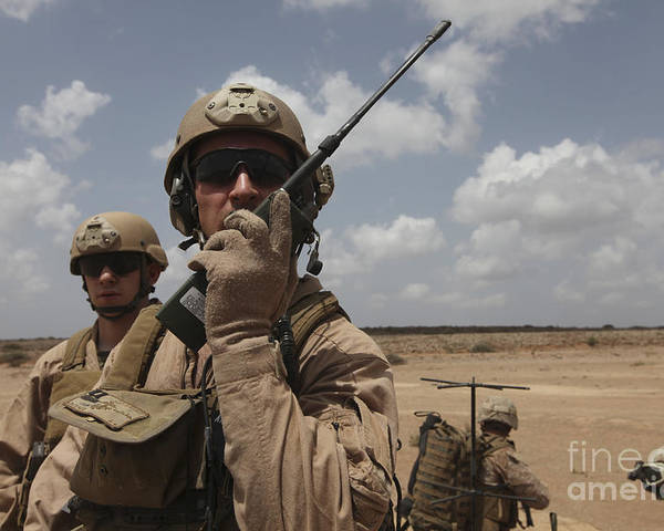 Deployment Poster featuring the photograph U.s. Marine Uses A Radio In Djibouti by Stocktrek Images