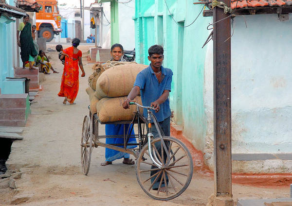 Houses Ghani Bags Man Women Child Lorry Wheels Cycle Cart Orange Red Blue Black Green Emerald Green White Street Brown Poster featuring the photograph Village Street by Johnson Moya