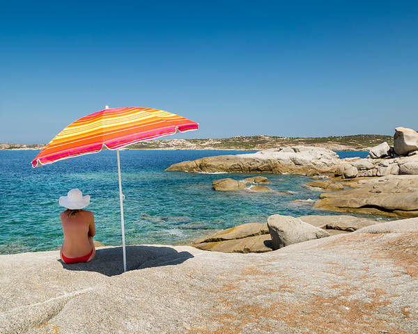 Arinella Poster featuring the photograph Woman In Red Bikini And White Hat Under Parasol Looking Out To S by Jon Ingall