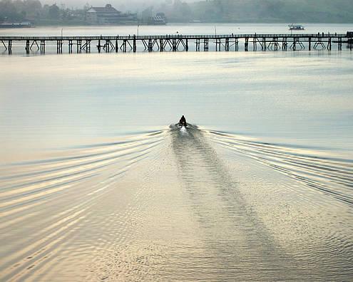 Bridge Poster featuring the photograph A Boat Approaching Mon Bridge In Sangkhlaburi by Jirawat Cheepsumol