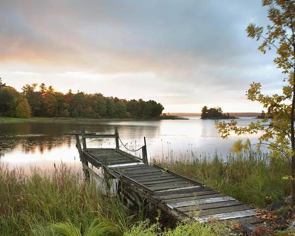 Sunrise Poster featuring the photograph A Dock On A Lake At Sunrise Near Wawa by Susan Dykstra