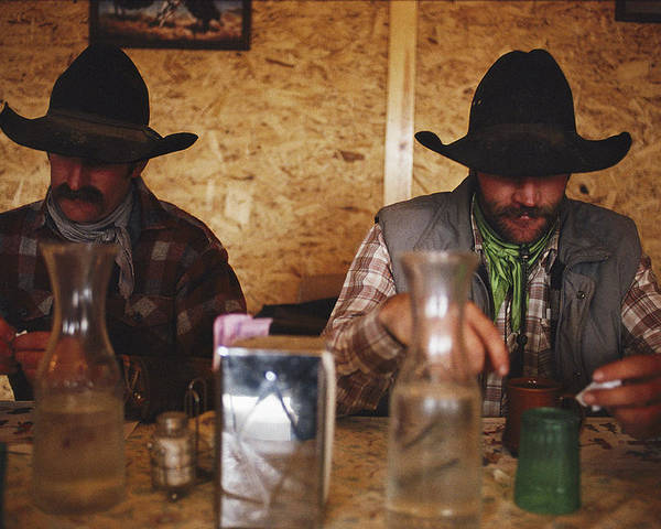Model Released Photography Poster featuring the photograph A Pair Of Cowboys Enjoy A Cup Of Coffee by Joel Sartore