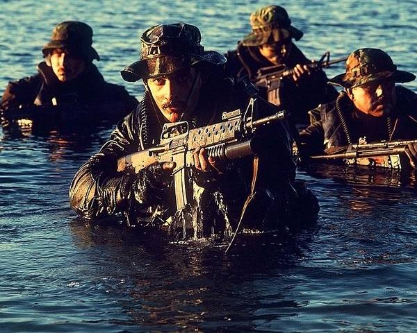History Poster featuring the photograph Us Navy Seal Team Emerges From Water by Everett