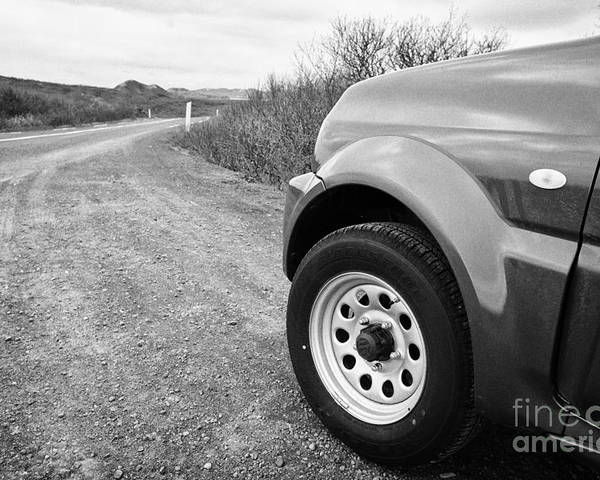 Wheel Poster featuring the photograph Wheel Of Small 4x4 Vehicle Driving On Gravel Road Onto Main Road Reykjavik Iceland by Joe Fox