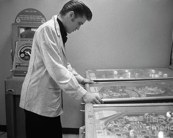 Elvis Presley Poster featuring the photograph Elvis Presley playing pinball 1956 by The Harrington Collection