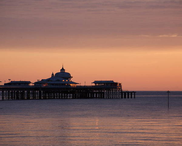 Sea Poster featuring the photograph Llandudno pier at dawn by Christopher Rowlands