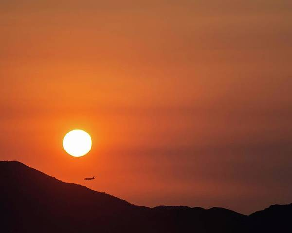Sunset Poster featuring the photograph Red sunset and plane in flight by Hannes Roeckel