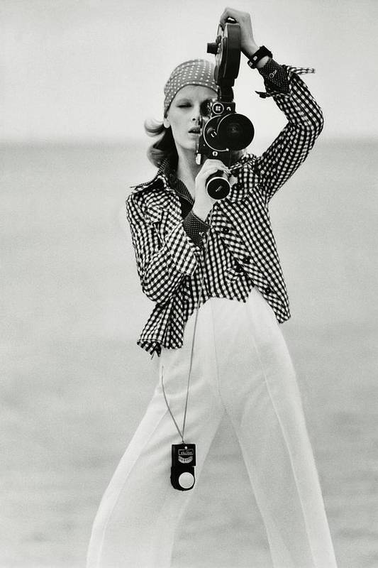 Fashion Poster featuring the photograph A Model Looking Through A Beaulieu Camera Wearing by Gianni Penati