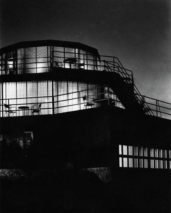 Home Poster featuring the photograph The Exterior Of A Spiral House Design At Night by Eugene Hutchinson