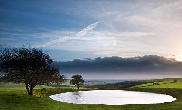Landscape Poster featuring the photograph Naturally Formed Dew Pond In Countryside Landscape With Moody Sk by Matthew Gibson