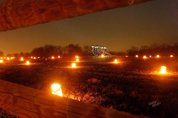 Looking Through A Split-rail Fence At A Solitary Cannon That Sits In The Middle Of This Field And Is Surrounded By Hundreds Of Luminaries. Each Year 23 Poster featuring the photograph Solitary Cannon 12 by Judi Quelland