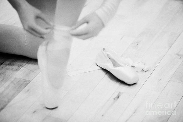 Ballet Poster featuring the photograph Student Putting On Pointe Shoes At A Ballet School In The Uk by Joe Fox