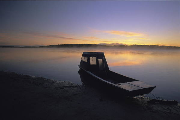 Boats Poster featuring the photograph A Boat Sits On The Calm Yukon River by Michael Melford