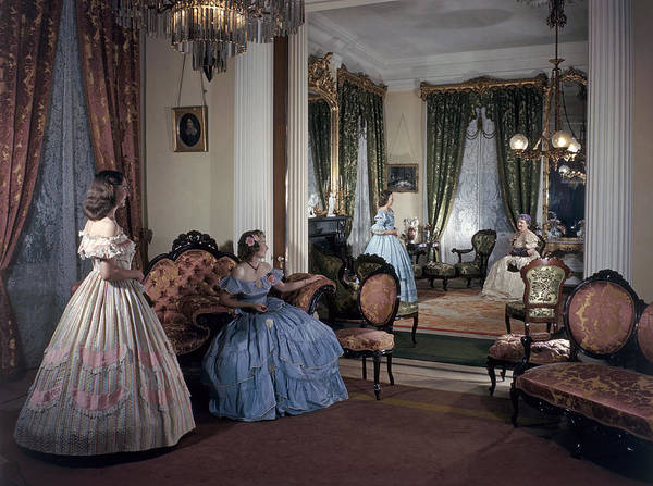 Indoors Poster featuring the photograph Women In Period Costumes Sit In An by Willard Culver