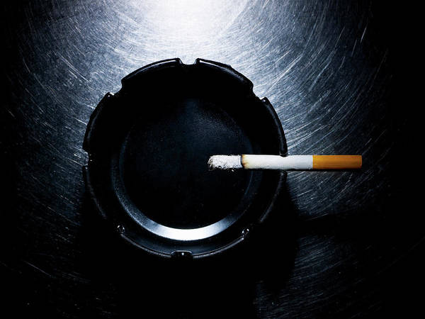 Horizontal Poster featuring the photograph Lit Cigarette And Ashtray On Stainless Steel. by Ballyscanlon