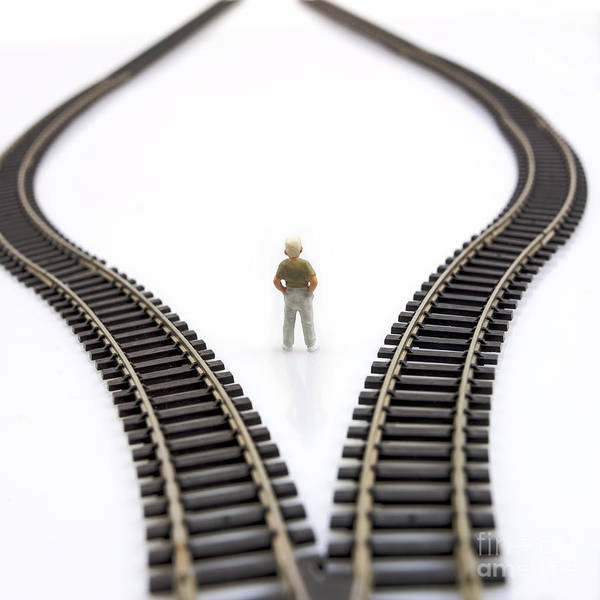 Decides Poster featuring the photograph Figurine Between Two Tracks Leading Into Different Directions Symbolic Image For Making Decisions. by Bernard Jaubert
