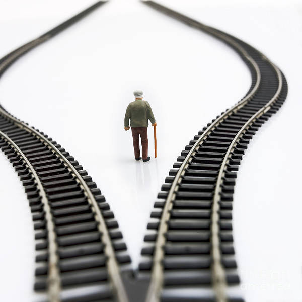Stick Poster featuring the photograph Figurine Between Two Tracks Leading Into Different Directions Symbolic Image For Making Decisions. by Bernard Jaubert