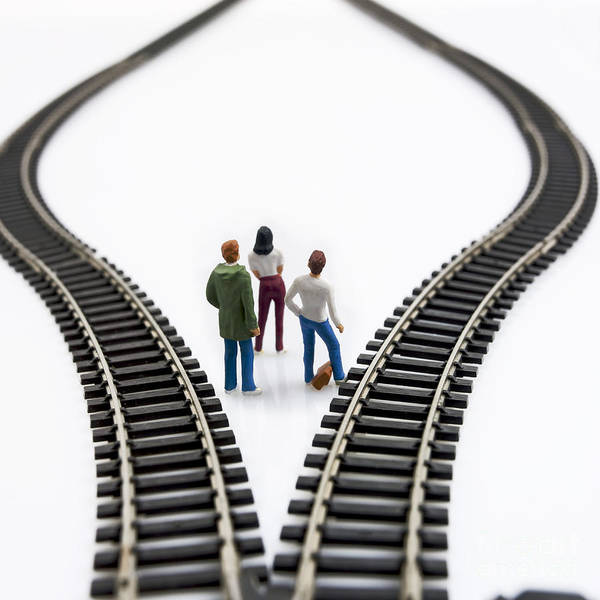 Reflective Poster featuring the photograph Figurines Between Two Tracks Leading Into Different Directions Symbolic Image For Making Decisions. by Bernard Jaubert