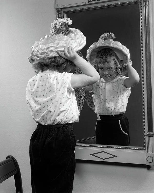 Photography Poster featuring the photograph 1950s Little Girl Trying On Hat Looking by Vintage Images