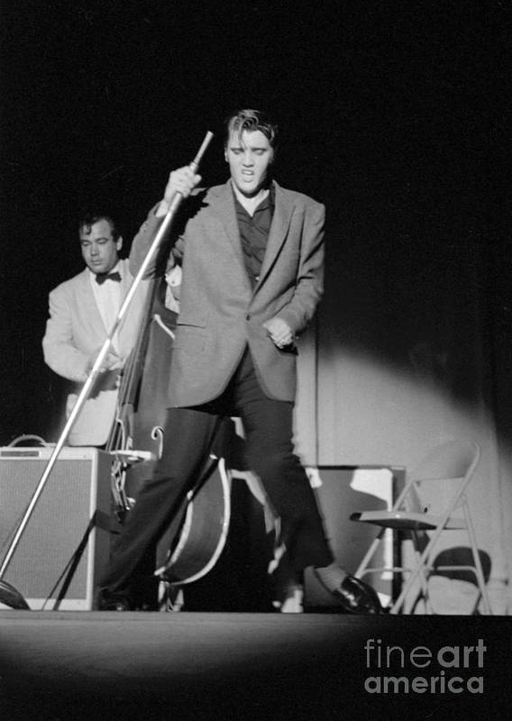 Elvis Presley Poster featuring the photograph Elvis Presley and Bill Black performing in 1956 by The Harrington Collection