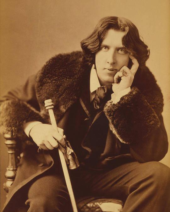 Oscar; Wilde; Irish; Writer; Poet; Author; Dandy; Cane; Fur; Trimmed; Coat; Victorian; Portrait; Three; Quarter; Length; Photograph; Sepia; Black; White Poster featuring the photograph Oscar Wilde 1882 by Napoleon Sarony