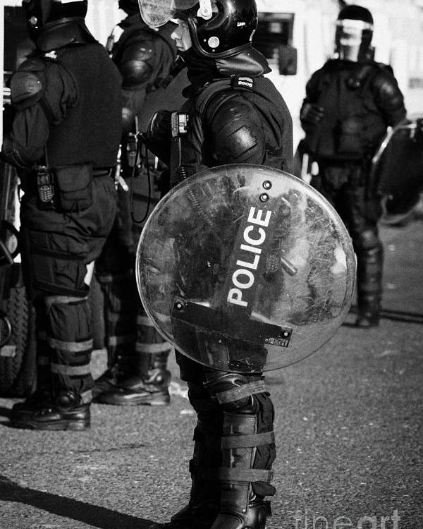 Northern Poster featuring the photograph Psni Officer In Full Riot Gear With Shield On Crumlin Road At Ardoyne Shops Belfast 12th July by Joe Fox