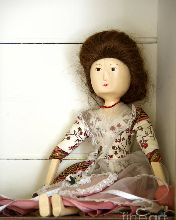 Doll; Toy; Wood; Wooden; Painted; Hair; Gentry; Colonial; Caucasian; Sit; Sitting; Shelf; Pretty; Brunette; Beautiful; Feminine; Dress; Necklace; Stare; Staring; Tiny; Female; Woman; Lady; Store; Toy Room Poster featuring the photograph Wooden Doll by Margie Hurwich