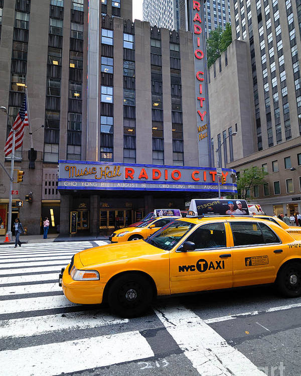 Building Poster featuring the photograph Yellow Cabs Pass In Front Of Radio City Music Hall by Amy Cicconi