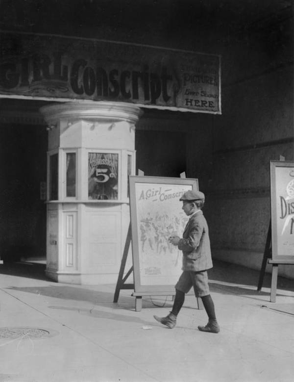 1910s Movies Poster featuring the photograph Boy In Front Of A Movie Theater Showing by Everett