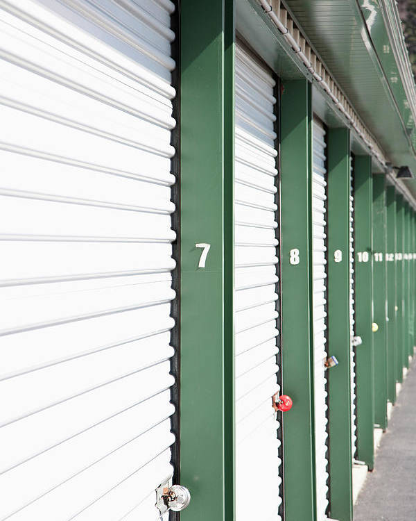 Vertical Poster featuring the photograph A Row Of Locked Storage Units At A Self Storage Facility by Frederick Bass